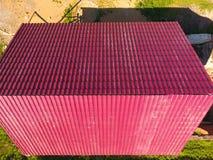 Une maison avec un toit rouge fait de feuillards ondulés Toit de profil ondulé en métal Tuiles en métal Photographie stock libre de droits