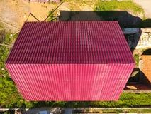 Une maison avec un toit rouge fait de feuillards ondulés Toit de profil ondulé en métal Tuiles en métal Image stock