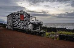 Une maison de lave avec les portes et les volets rouges sous le Pico Photo stock