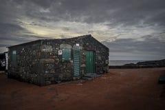 Une maison de lave avec les portes et les volets verts sous le Pico Photo libre de droits
