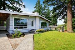 Une maison de niveau avec l'équilibre de voie de garage et la pelouse soignée Photographie stock