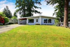Une maison de niveau avec l'équilibre de voie de garage et la pelouse soignée Images stock