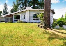 Une maison de niveau avec l'équilibre de voie de garage et la pelouse soignée Photo libre de droits