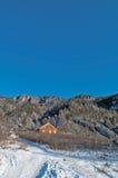 Une maison en bois en montagnes, en hiver Image libre de droits
