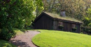 Une maison en bois sur une pelouse aménagée en parc dessous avec un chemin Images stock