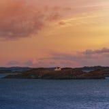 Une maison isolée sur une petite île au coucher du soleil Photos libres de droits