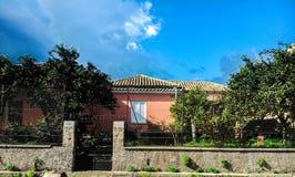 Une maison orange, un ciel bleu et des arbres Image libre de droits