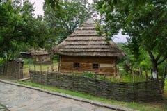 Une maison rurale sous un toit couvert de chaume avec de petites fenêtres dans le mur derrière une barrière d'acacia dans un sect Image libre de droits