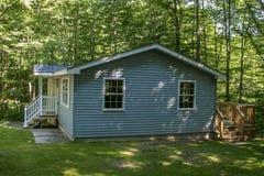 Une maison suburbaine bleue sur une pelouse herbeuse Image libre de droits