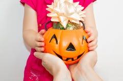 Une maman de petite fille étire un potiron rempli de sucrerie Halloween image stock