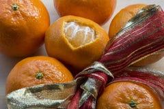 Une mandarine avec la peau sous la forme de coeur avec le ruban rouge-jaune Image stock