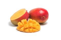 Une mangue mûre entière et une moitié découpée en tranches d'une mangue Photographie stock