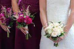 Une mariée et les fleurs de sa demoiselle d'honneur Images libres de droits