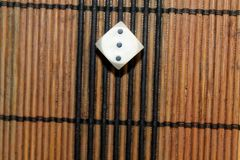 Une matrice en plastique blanche sur le fond brun de conseil en bois Six cubes en côtés avec les points noirs mer du nord proche  photographie stock