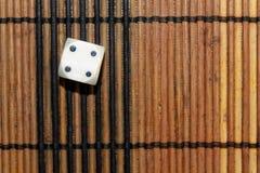 Une matrice en plastique blanche sur le fond brun de conseil en bois Six cubes en côtés avec les points noirs Numéro 4 Images libres de droits