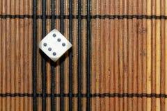 Une matrice en plastique blanche sur le fond brun de conseil en bois Six cubes en côtés avec les points noirs Numéro 6 Photos libres de droits