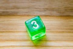 Une matrice jouante hexagone verte translucide sur un backgroun en bois photo stock