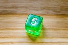 Une matrice jouante hexagone verte translucide sur un backgroun en bois photos stock