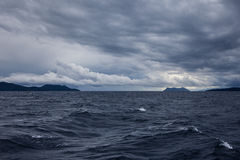 Une mer orageuse avec les nuages et les îles foncés Photo libre de droits