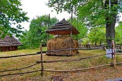 Une meule de foin sous un auvent couvert de toit couvert de chaume dans la cour d'un manoir rural est clôturée avec une haie avec images stock