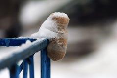 Une mitaine sur une barrière bleue couverte de neige Photos stock