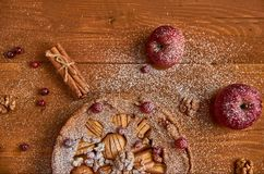 Une moitié de tarte aux pommes savoureuse avec les canneberges fraîches et les noix décorées des pommes et de la cannelle Tarte a Image stock