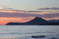 Une montagne dépassant de la mer avec un ciel orange photo stock