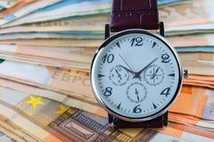 Une montre-bracelet sur un bouchon d'euro factures images libres de droits