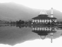 Une mosquée blanche d'amd noir par le lac avec une réflexion Photos libres de droits
