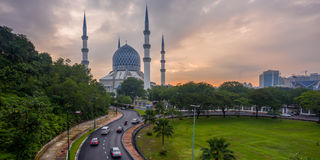 Une mosquée et un lever de soleil nuageux avec des voitures passant des routes Photographie stock libre de droits