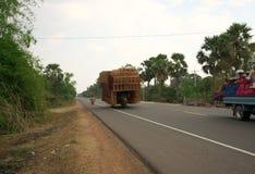 Une moto fonctionne sur l'autoroute nationale 6 dans un bon nombre de chargement du Cambodge de boîtes de rotin photo stock