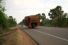 Une moto fonctionne sur l'autoroute nationale 6 dans un bon nombre de chargement du Cambodge de boîtes de rotin photos libres de droits