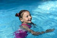 Une natation de petite fille dans une eau lumineuse de turquoise d'une piscine Photo stock