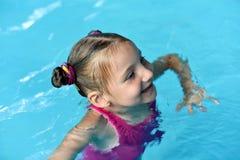 Une natation de petite fille dans une eau lumineuse de turquoise d'une piscine Photos libres de droits