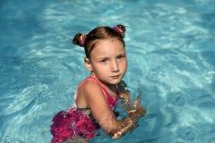 Une natation de petite fille dans une eau lumineuse de turquoise d'une piscine Photo libre de droits