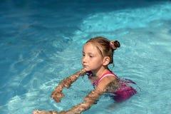 Une natation de petite fille dans une eau lumineuse de turquoise d'une piscine Images stock