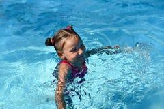 Une natation de petite fille dans une eau lumineuse de turquoise d'une piscine Image stock