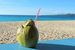 Une noix de coco avec une fibre de coco comme boisson non alcoolisée sur une plage tropicale Photos stock