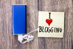 Une note ayant l'amour des mots I Blogging est présente avec la banque de puissance sur la surface boisée brune exprime les intér Image stock