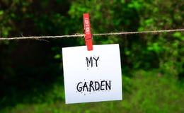 Une note indiquant mon jardin accrochant sur une ficelle de vintage chevillée par une cheville rouge avec l'inscription fraîche e Images libres de droits