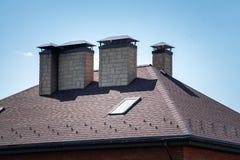 Une nouvelle maison avec le toit carrelé, la cheminée, la ventilation pour le contrôle de chaleur, le débordement et la protectio image stock