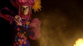 Une nuit par la danse mystique du feu exécute une fille gracieuse dans un costume lumineux et un masque d'or banque de vidéos
