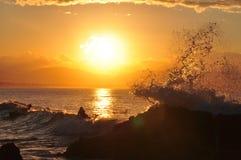 Une onde d'océan éclabousse outre des roches dans le coucher du soleil d'or Photos stock