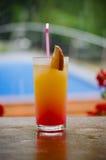 Une orange avec le verre de cocktail rouge se reposant sur la table autour de la piscine Photographie stock