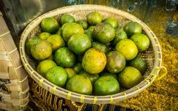 Une orange verte sur le panier en bambou ou en bois sur le marché traditionnel de Java-Centrale Photos stock
