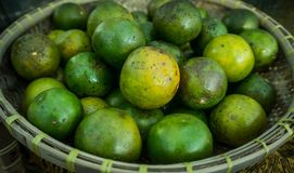 Une orange verte sur le panier en bambou ou en bois sur le marché traditionnel de Java-Centrale avec la couleur chaude Photo stock