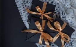 Une ouverture de noir de cadeau, enveloppée dans un ruban d'or images stock