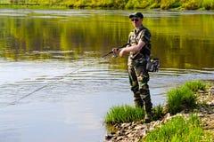 Une pêche d'homme à la rivière Photo stock