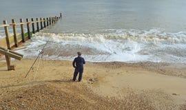 Une pêche d'homme de plage avec la tige et le repos Image stock