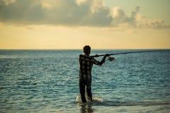 Une pêche de pêcheur à la ligne sur la plage Image stock